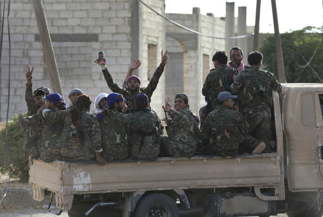 FILE - In this July 22, 2017, file photo, Arab and Kurdish fighters with the U.S.-backed Syrian Democratic Forces (SDF), move to the front line to battle Islamic State group militants, in Raqqa, Syria. (AP Photo/Hussein Malla, File)