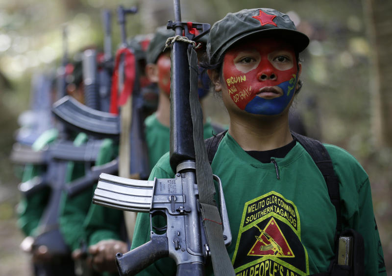 FILE - In this Nov. 23, 2016, file photo, members of the New People's Army communist rebels with face painted to conceal their identities, march with their firearms before a news conference held at their guerrilla encampment tucked in the harsh wilderness of the Sierra Madre mountains southeast of Manila, Philippines. Justice officials have asked a court to formally designate the Communist Party of the Philippines and its armed wing, the New People's Army, as terrorist groups in a move that could further damage chances of a resumption of stalled peace talks. (AP Photo/Aaron Favila, File)