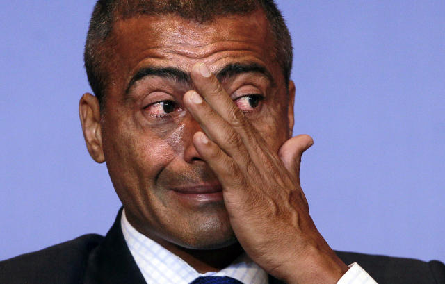 FILE - In this Dec. 23, 2011 file photo, Brazil's congressman and former soccer star Romario wipes a tear during a news conference in Rio de Janeiro, Brazil. In the latest chapter of a spat between past Brazil football greats, Ronaldo is publicly criticizing former teammate Romario for making another attack on him, this time over an alleged broken promise to provide free tickets for people with disabilities during the World Cup. (AP Photo/Victor R. Caivano, File)