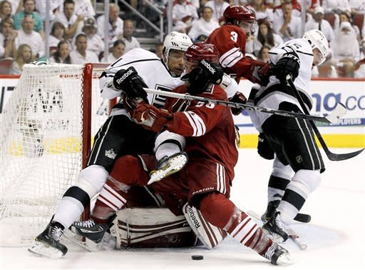 Los Angeles Kings' Jordan Nolan (71) pulls Phoenix Coyotes' Derek Morris (53) down as Keith Yandle (3) and Kings' Brad Richardson (15) tangle in the second period during Game 2 of the NHL hockey Stanley Cup Western Conference finals, Tuesday, May 15, 2012, in Glendale, Ariz. (AP Photo/Ross D. Franklin)