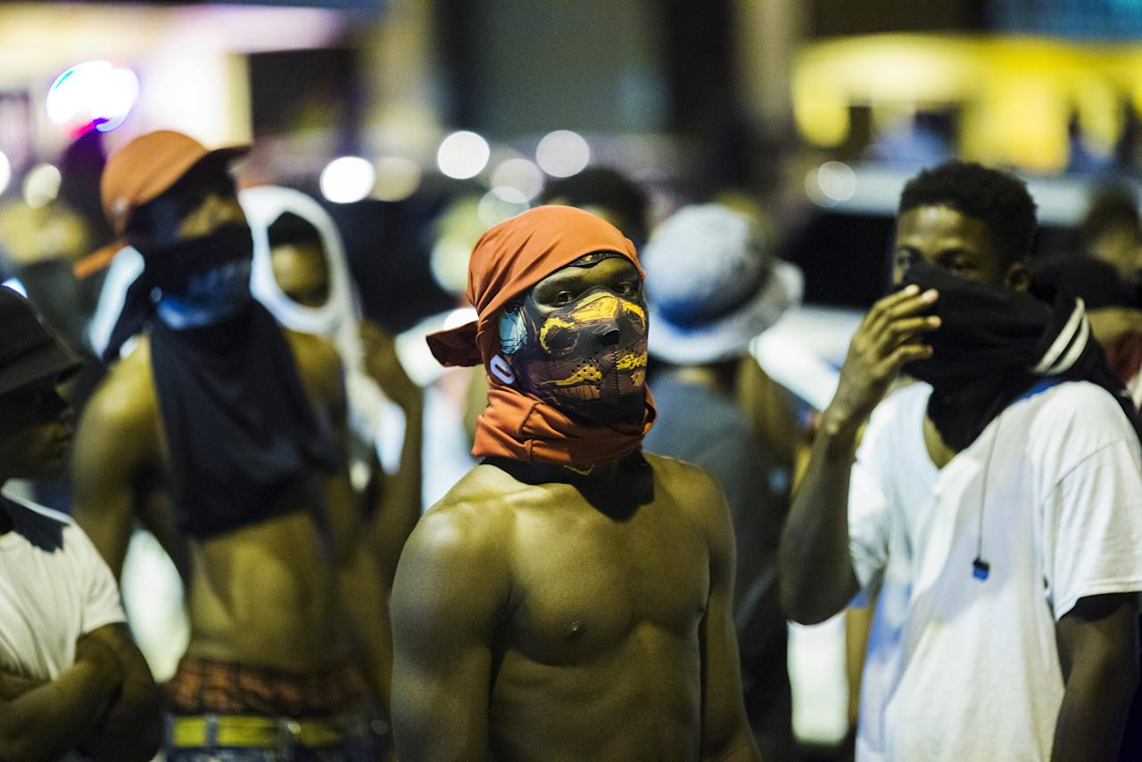Young men wait to see to see what happens during another night of demonstrating in Ferguson, Missouri, August 12, 2015. REUTERS/Lucas Jackson