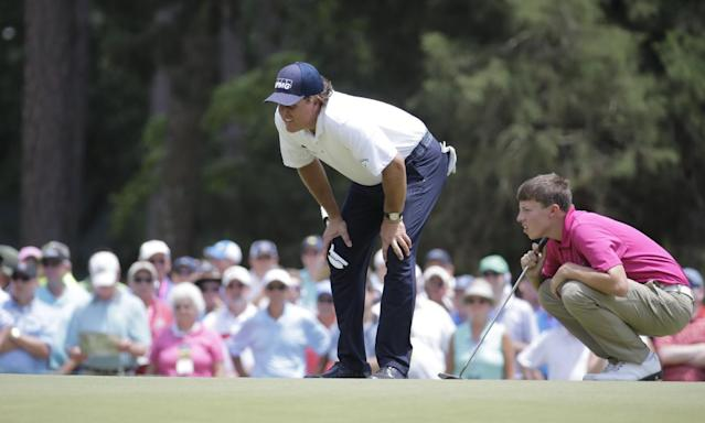 Phil Mickelson, left and Amateur, Matthew Fitzpatrick, England, line up their putts on the second hole during the second round of the U.S. Open golf tournament in Pinehurst, N.C., Friday, June 13, 2014. (AP Photo/Eric Gay)