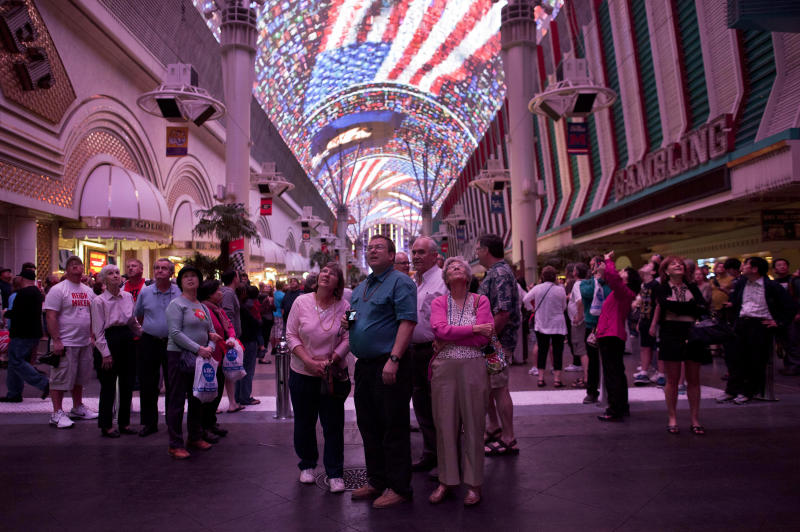 FILE - In this Thursday, March 22, 2012 file photo, tourists stop to watch the canopy light show at the Fremont Street Experience in Las Vegas. Despite some recent diversification, Nevada's economy is more concentrated than virtually any other state. The tourism/gambling sector accounts for more than one-quarter of Nevada's 1.14 million non-farm jobs, and 13 of the 20 largest employers are casino/hotel companies. President Barack Obama and his Republican rival, Mitt Romney, have visited the state, competing strenuously for Nevada's six electoral votes in what has become one of the most intense swing-state contests. (AP Photo/Julie Jacobson, File)