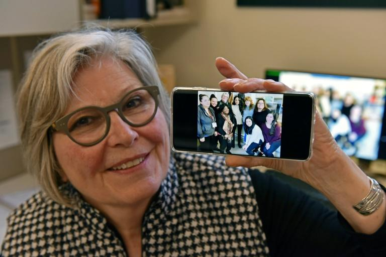 Kate Gibson, acting executive director of Downtown Eastside Women's Centre in Vancouver, shows a photo taken with Meghan Markle during her visit (AFP Photo/Don MacKinnon)