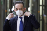 German Foreign Minister Heiko Maas prepares to take off his protective face mask as he arrives for a meeting of EU foreign ministers at the European Council building in Brussels, Monday, Feb 22, 2021. European Union foreign ministers on Monday will look at options for imposing fresh sanctions against Russia over the jailing of opposition leader Alexei Navalny as the 27-nation bloc considers the future of its troubled ties with the country. (Yves Herman, Pool via AP)