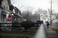 A banner decorated with the image of Jesus hangs outside a home as a mail carrier walks down the street in Huntington, W.Va., Wednesday, March 17, 2021. This beleaguered city offered a glimmer of hope to a nation impotent to contain its decades-long addiction catastrophe killing by the tens of thousands. The federal government honored Huntington as a model city to emulate. They won awards for this work. Other places came to study their success. (AP Photo/David Goldman)