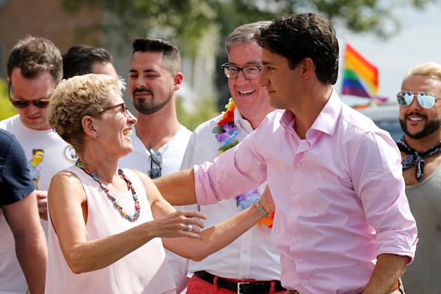 Canada's Prime Minister Justin Trudeau (R) embraces Ontario Premier Kathleen Wynne (L) as Ottawa Mayor Jim Watson (C) looks on during the Ottawa Pride Parade in Ottawa, Ontario, Canada, August 27, 2017. REUTERS/Chris Wattie