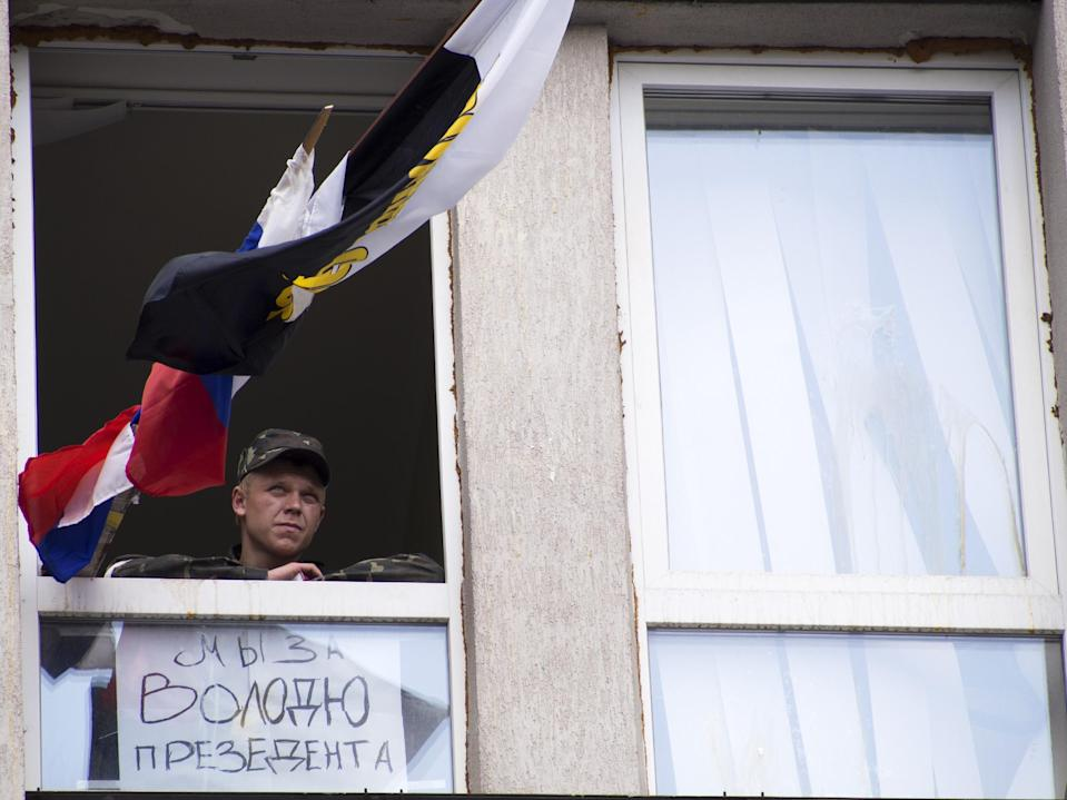 """A pro-Russian activist looks through a broken window of the Ukrainian regional office of the Security Service decorated by Russian and Donetsk region's flags and a small poster reading """"We are for president Volodya (Vladimir Putin) """" in Luhansk, 30 kilometers (20 miles) west of the Russian border, in Ukraine, Wednesday, April 9, 2014. Ukrainian Interior Minister Arsen Avakov said the standoff in Luhansk and the two neighboring Russian-leaning regions of Donetsk and Kharkiv must be resolved within two days.(AP Photo/Igor Golovniov)"""