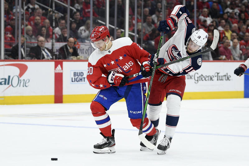Washington Capitals center Lars Eller (20), of Denmark, and Columbus Blue Jackets center Pierre-Luc Dubois (18) vie for the puck during the first period of an NHL hockey game Friday, Dec. 27, 2019, in Washington. (AP Photo/Nick Wass)