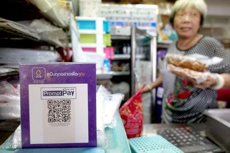 An advertisement board displaying a QR code is seen as a vendor works at a market in Bangkok, Thailand, November 22, 2017. REUTERS/Athit Perawongmetha