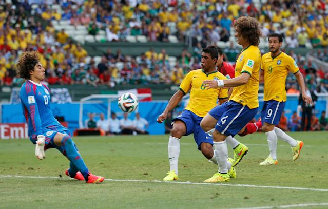 Mexico's Guillermo Ochoa (L-R) makes a save in front of Brazil's Paulinho, David Luiz and Fred during their 2014 World Cup Group A soccer match at the Castelao arena in Fortaleza June 17, 2014. REUTERS/Sergio Moraes (BRAZIL - Tags: SOCCER SPORT WORLD CUP)