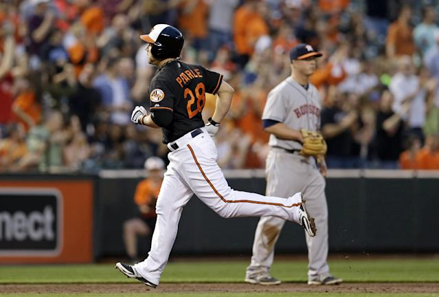 Baltimore Orioles' Steve Pearce, left, rounds the bases past Houston Astros third baseman Matt Dominguez after hitting a solo home run in the third inning of baseball game, Friday, May 9, 2014, in Baltimore. (AP Photo/Patrick Semansky)