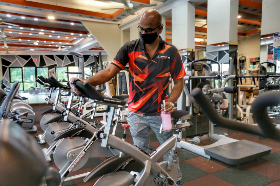 Enrich Fitness gym owner Krishna Kumar sanitises his gym equipments to comply with NSC SOPs February 12, 2021. — Picture by Ahmad Zamzahuri