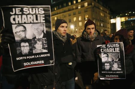 """People hold placards with pictures of victims which read """"I am Charlie"""", to pay tribute to victims in front of the Brandenburg Gate near the French embassy at Pariser Platz in Berlin January 7, 2015, following a shooting by gunmen at the offices of weekly satirical magazine Charlie Hebdo in Paris. REUTERS/Fabrizio Bensch"""