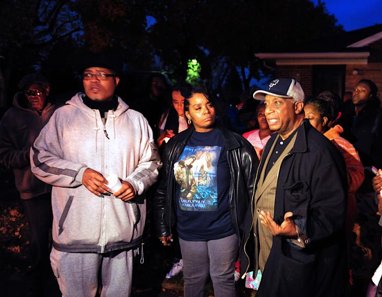 In this Wednesday, Nov. 6, 2013 photo, from left, Pastor W. J. Rideout, Renisha McBride's aunt Bernita Spinks and Ron Scott speak to the media during a vigil in Dearborn Heights, Mich., for Renisha McBride in the front of the home where she shot early Saturday. No charges have been filed after authorities said McBride, of Detroit, was killed by a shotgun blast to the face early Saturday in Dearborn Heights. According to police, the homeowner told investigators that he thought someone was trying to break into his home and accidentally discharged the gun.(AP Photo/Detroit News, Ricardo Thomas) DETROIT FREE PRESS OUT; HUFFINGTON POST OUT