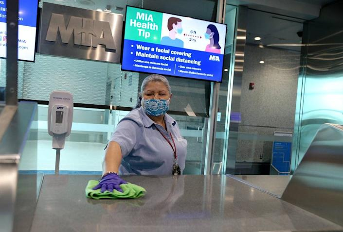 Alba Rios, an employee with CW Facility Services, sanitizes the counters at an American Airlines Concourse A gate at Miami International Airport, as American Airlines hosted the media to highlight the changes to the customer journey to ensure the well being of travelers as they return to the skies amid a surge of COVID cases in Florida, on Tuesday, June 30, 2020.