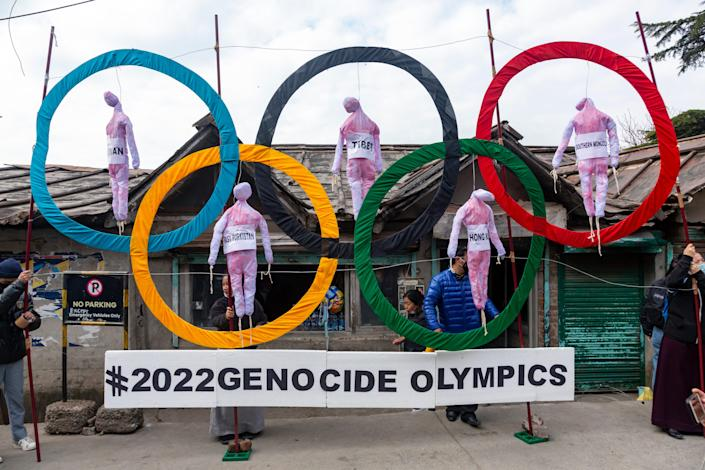 Exile Tibetans use the Olympic Rings as a prop as they hold a street protest against the holding of 2022 Winter Olympics in Beijing in Dharmsala, India, on Feb. 3. Some kind of boycott is almost sure to affect next year's Beijing Winter Olympics. It's driven by the widely reported internment of several million Muslim Uyghurs and other ethnic minorities in China, which has been termed a genocide by numerous governments and human rights groups.