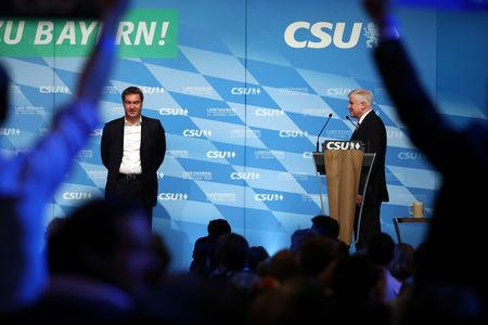 FILE PHOTO: Leader of the Christian Social Union (CSU) Horst Seehofer and Bavarian State Prime Minister Markus Soeder appear on stage during a CSU election campaign rally in  Munich, Germany, October 12, 2018. REUTERS/Michael Dalder