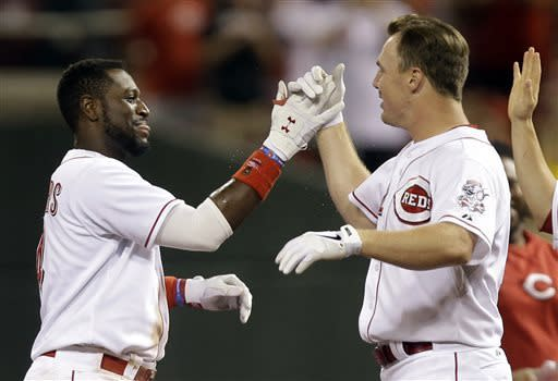 Cincinnati Reds' Jay Bruce, right, congratulates Brandon Phillips after Phillips drove in the winning run with a single off Pittsburgh Pirates relief pitcher Vin Mazzaro in the 13th inning of a baseball game, Wednesday, June 19, 2013, in Cincinnati. Bruce had tied the game with a home run in the bottom of the ninth to send it to extra innings. (AP Photo/Al Behrman)