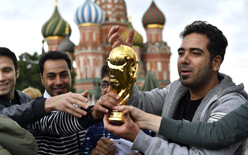 Iranian fans hold a replica trophy on Red Square ahead of the World Cup, which starts Thursday - AFP