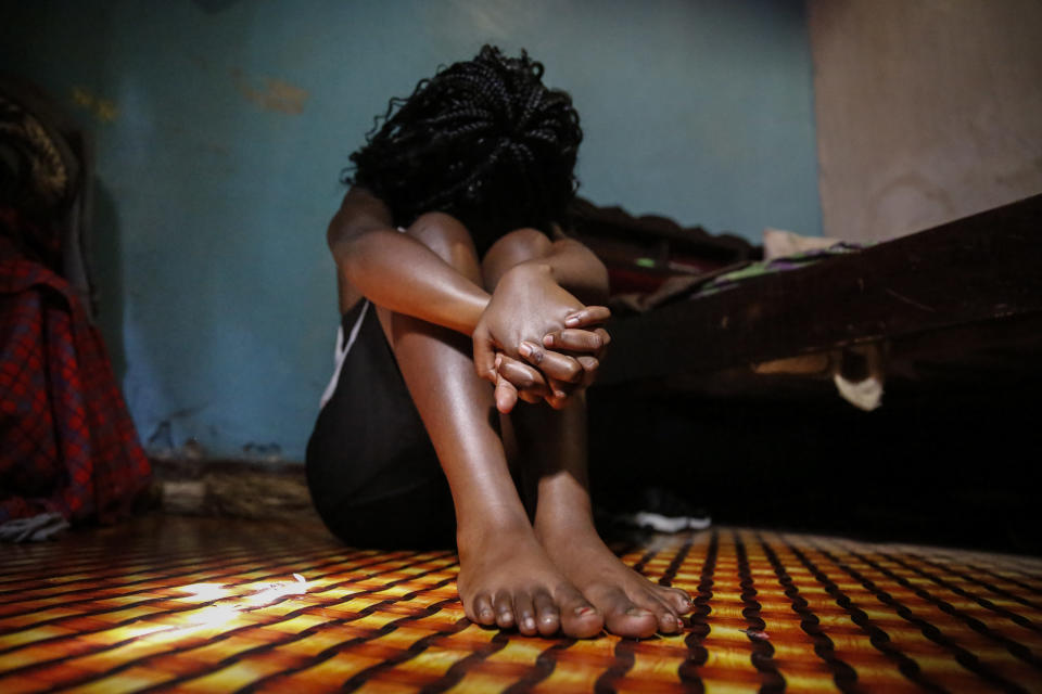 A teenage girl who became a sex worker after schools in Kenya were closed in March due to coronavirus restrictions, sits in the rented room where she and others work, in Nairobi, Kenya Thursday, Oct. 1, 2020. The girls saw their mothers' sources of income vanish when Kenya's government restricted movement to prevent the spread of the virus, and now engage in the sex work to help with household bills. (AP Photo/Brian Inganga)