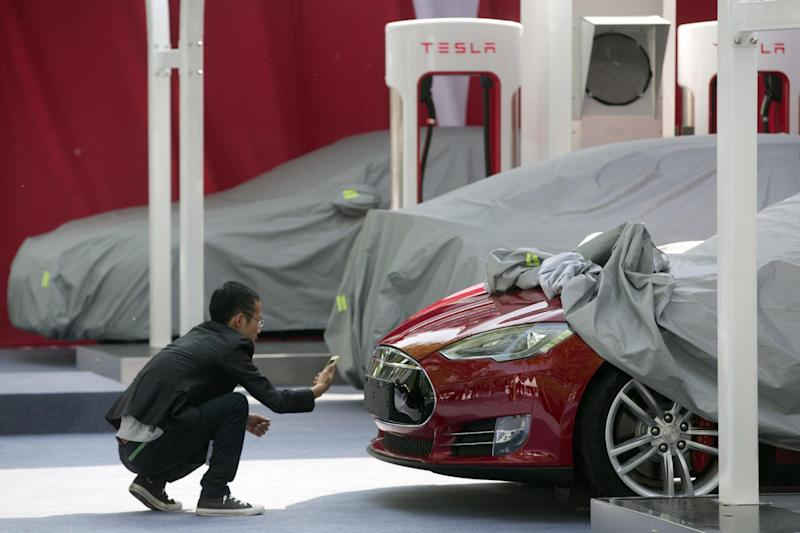 A man takes a photo of the logo on a Tesla Model S sedan at an event in Beijing, China, Tuesday, April 22, 2014. Tesla Motors delivered its first eight electric sedans to customers in China on Tuesday and CEO Elon Musk said the company will build a nationwide network of charging stations and service centers as fast as it can. (AP Photo/Ng Han Guan)