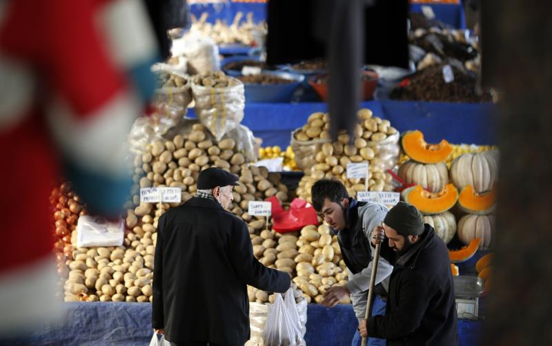 A vendor sells potatoes and other vegetables to a customer in an open market in central Ankara