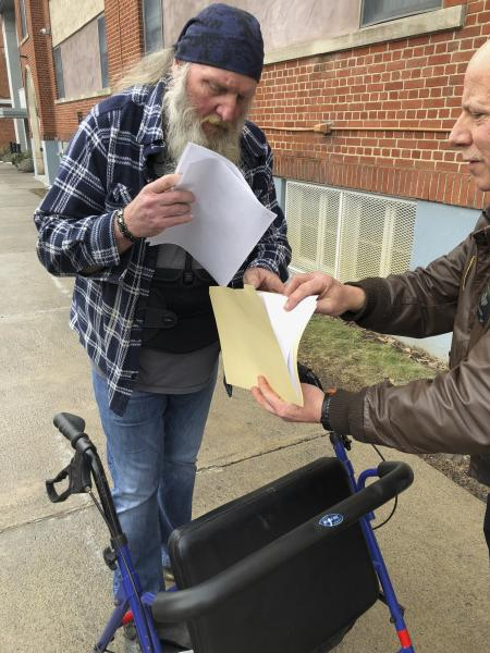 Ray Kemble, left, and Craig Stevens look through papers outside the Susquehanna County Courthouse in Montrose, Pennsylvania, on Feb. 4, 2018. A gas driller backed off its demand to have Kemble, a Pennsylvania homeowner who's long accused the company of polluting his water, thrown in jail over his failure to submit to questioning as part of the company's $5 million lawsuit against him. (AP Photo/Michael Rubinkam) (AP Photo/Michael Rubinkam)