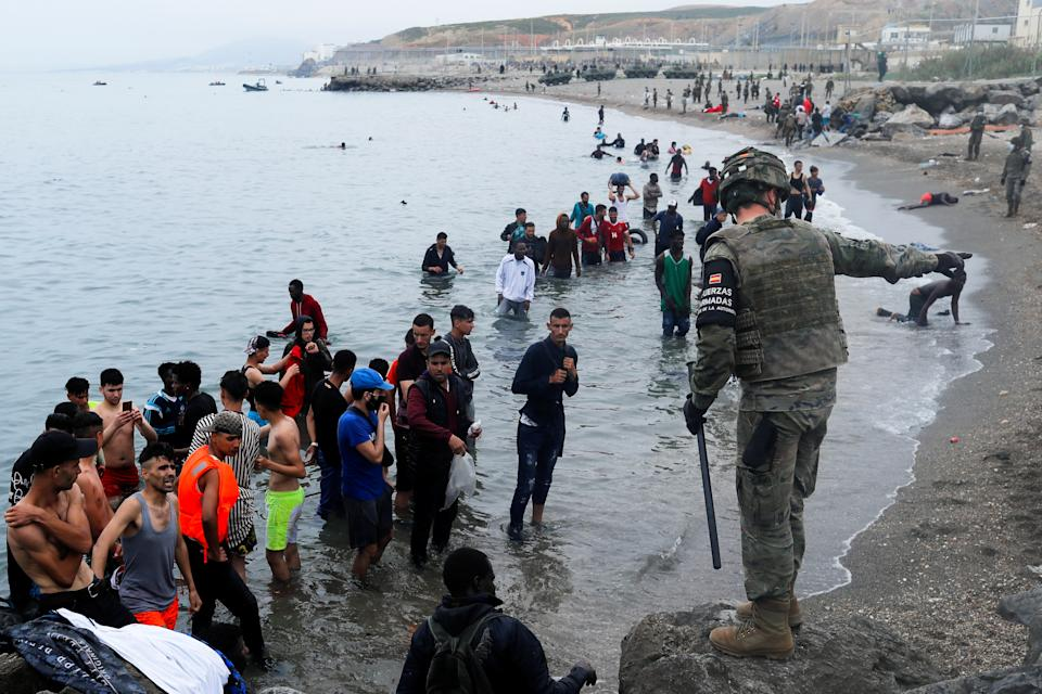 A Spanish legionnaire indicates the direction to follow to Moroccan citizens on El Tarajal beach, as they get out of the water on the Spanish side of the fence between the Spanish-Moroccan border, after thousands of Moroccans swam across this border on Monday, in Ceuta, Spain, May 18, 2021. REUTERS/Jon Nazca