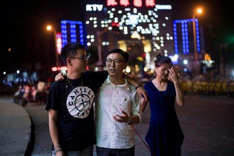 """""""Having two sons is even better. My one son has turned into two,"""" says He Fenglanm who admits she initially struggled to cope when her son Li Tao (C) told her he was gay. Duan Rongfeng (L) and Li Tao (C) walking their dog together with Li Tao's mother, He Fenglanm in Shanghai.Coming-out in family-oriented China remains traumatic, often tearing households apart or leading to gay suicides. The fears are so intense that advocacy groups estimate millions of gays marry heterosexuals, hiding their identities in miserable unions that often fail"""