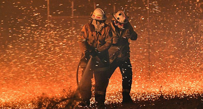 Firefighters struggle against the strong wind in an effort to secure nearby houses from bushfires near the town of Nowra.