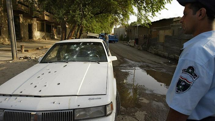 An Iraqi policeman stands by the bullet riddled car of two women allegedly shot dead by private security guards in central Baghdad, 09 October 2007
