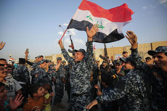 <p>JUL. 2, 2017 – Members of the Iraqi federal police dance with children and a national flag during a celebration in the Old City of Mosul, where the gruelling battle to retake Iraq's second city from Islamic State (IS) group fighters is now nearing its end, on July 2, 2017. (Photo: Ahmad al-Rubaye/AFP/Getty Images) </p>