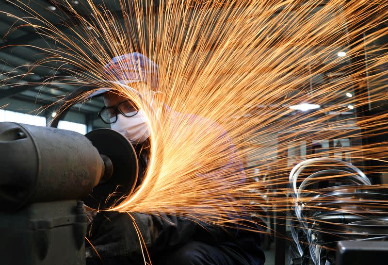 Worker wearing a face mask works on a production line manufacturing bicycle steel rim at a factory in Hangzhou, Zhejiang