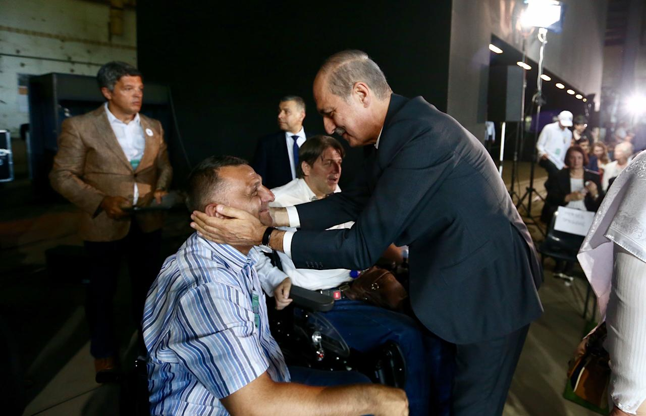 <p>Deputy Prime Minister of Turkey Numan Kurtulmus (R) meets with Bosnians during a ceremony, to mark the 22nd anniversary of the 1995 Srebrenica massacre, in an old battery factory, which was used as a headquarter by UN soldiers, in Potocari village of Srebrenica, Bosnia and Herzegovina on July 11, 2017. (Photo: Ahmet Bolat/Anadolu Agency/Getty Images) </p>