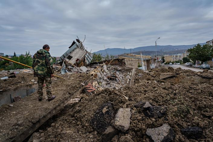 A man looks over a crater blast along a street in front of a residential area in Stepanakert.