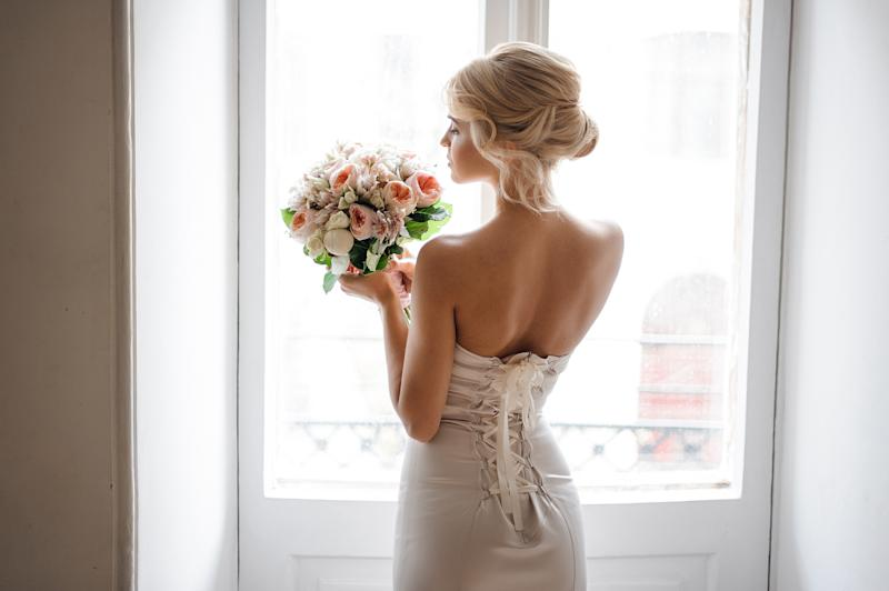 Back view of the elegant blonde bride dressed in a white dress holding a wedding bouquet on the background of window.