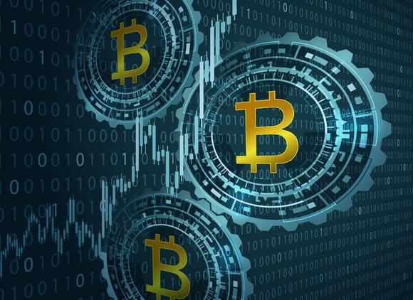 Three bitcoin logos on a background of binary code.