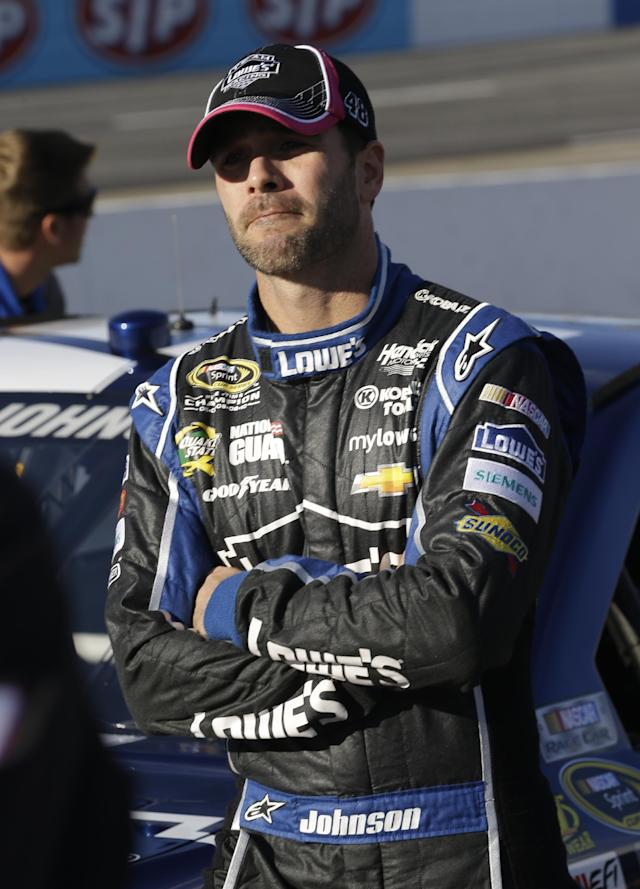 Jimmie Johnson talks with his crew during qualifying for Sunday's NASCAR Sprint Cup series auto race at Martinsville Speedway in Martinsville, Va., Friday, Oct. 25, 2013. (AP Photo/Steve Helber)