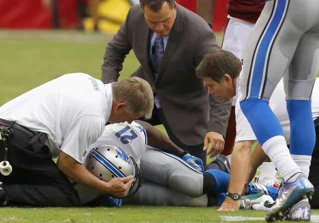 Detroit Lions' Reggie Bush (21) is attended to by training and medical staff after injuring his leg during the first half in an NFL football game against the Arizona Cardinals on Sunday, Sept. 15, 2013, in Glendale, Ariz. (AP Photo/Ross D. Franklin)