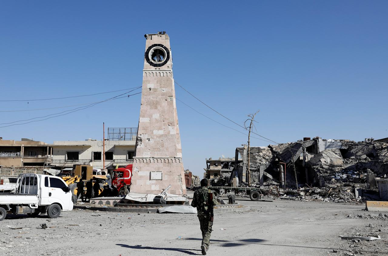 A fighter of Syrian Democratic Forces walks towards a clock tower in Raqqa, Syria October 18, 2017. Picture taken October 18, 2017.     REUTERS/Erik De Castro