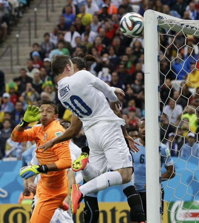 England's Wayne Rooney hits the bar with a header during the group D World Cup soccer match between Uruguay and England at the Itaquerao Stadium in Sao Paulo, Brazil, Thursday, June 19, 2014. (AP Photo/Thanassis Stavrakis)