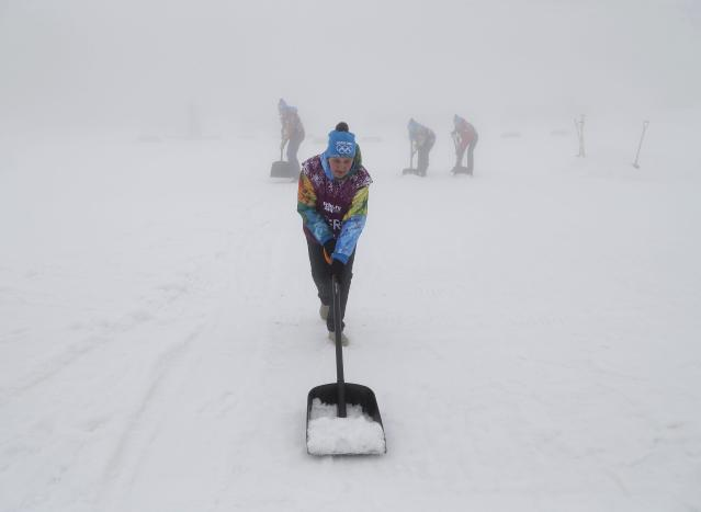 Workers shovel snow in thick fog at the Laura Cross Country Ski and Biathlon Center at the Sochi 2014 Winter Olympic Games, February 17, 2014. Organisers of the Sochi Olympics defied the odds when they battled unusually warm temperatures for a week but they were helpless against a winter fog that caused events to be postponed on Monday. The men's biathlon 15km mass start was called off for a second straight day due to thick fog. REUTERS/Stefan Wermuth (RUSSIA - Tags: OLYMPICS SPORT ENVIRONMENT SPORT BIATHLON TPX IMAGES OF THE DAY)