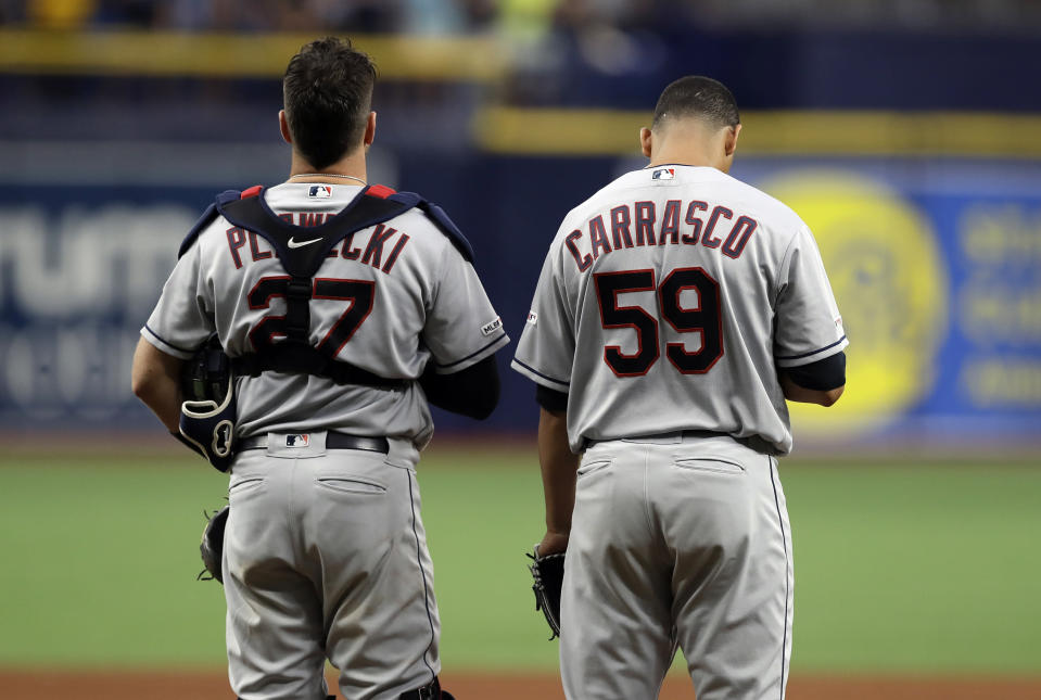 """Cleveland Indians pitcher Carlos Carrasco (59) stands with catcher Kevin Plawecki during the playing of """"God Bless America"""" in the seventh inning of a baseball game against the Tampa Bay Rays, Sunday, Sept. 1, 2019, in St. Petersburg, Fla. Carrasco is making his first appearance since May, when he was diagnosed with leukemia. (AP Photo/Chris O'Meara)"""