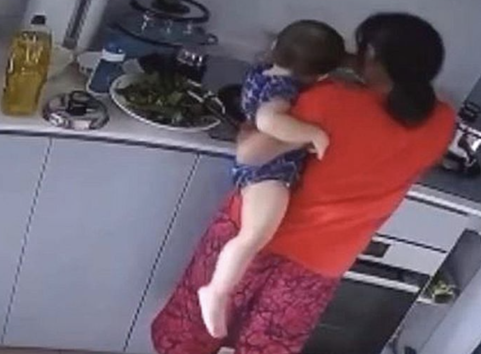 A screengrab of the CCTV recording showing the maid supposedly dipping the baby's hand into a pot. (PHOTO: Facebook)