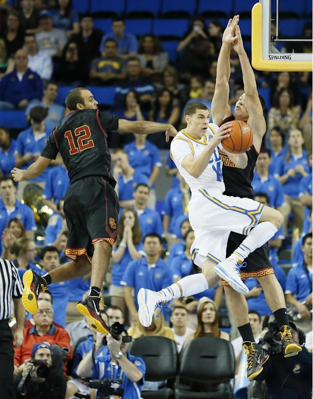 UCLA's Zach LaVine, center, goes to the hoop as Southern California's Julian Jacobs, left, and Nikola Jovanovic, right, defend during the first half of an NCAA college basketball game, Sunday, Jan. 5, 2014, in Los Angeles. (AP Photo/Danny Moloshok)