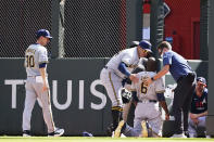 Milwaukee Brewers center fielder Lorenzo Cain (6) is attended to after an injury while trying to make a catch against Atlanta Braves' Adam Duvall during the fourth inning of Game 3 of a baseball National League Division Series, Monday, Oct. 11, 2021, in Atlanta. (AP Photo/John Bazemore)