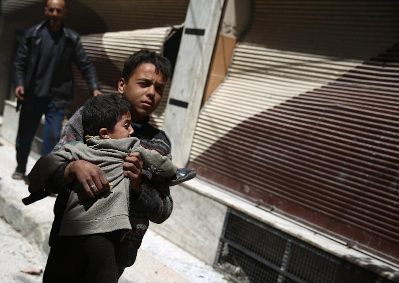 A Syrian boy carries a child while he runs for cover in the rebel-held area of Douma, east of the capital Damascus, as air strikes pound the city on April 22, 2015