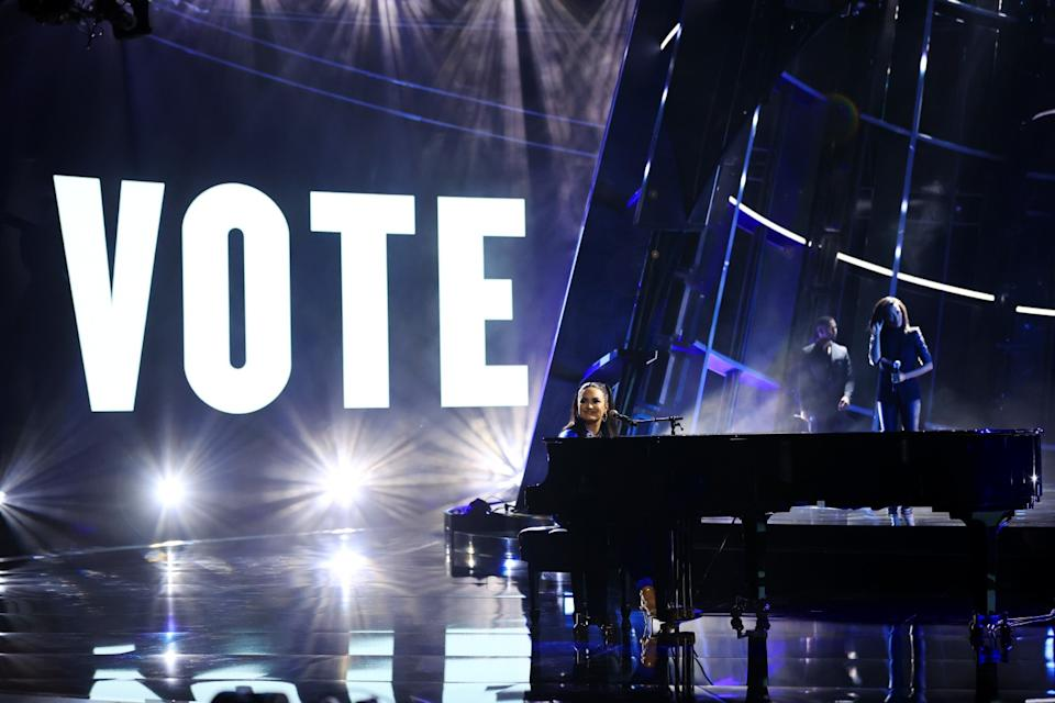 """Demi Lovato, backed by a huge """"Vote"""" sign, performs at the piano."""