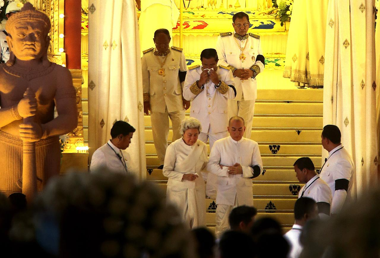 "Cambodian King Norodom Sihamoni, center right, son of the late King Norodom Sihanouk, and his mother, Queen Norodom Monineath, center left, with Cambodia's Prime Minister Hun Sen, covering his mouth, leave the crematorium where the body of the late former Cambodian King Norodom Sihanouk rests in Phnom Penh, Monday, Feb. 4, 2013. Hundreds of thousands of mourners gathered in Cambodia's capital Monday for the cremation of former King Norodom Sihanouk, the revered ""King-Father,"" who survived wars and the murderous Khmer Rouge regime to hold center stage in the Southeast Asian nation for more than half a century. (AP Photo/Wong Maye-E)"